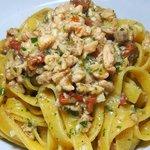 Tagliatelle con ragù di salmone e pomodorini secchi profumato all'aglio.