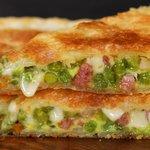 Torta salata in padella con piselli, pancetta e scamorza