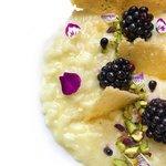 Risotto al parmigiano con more, pistacchi e parmigiano.